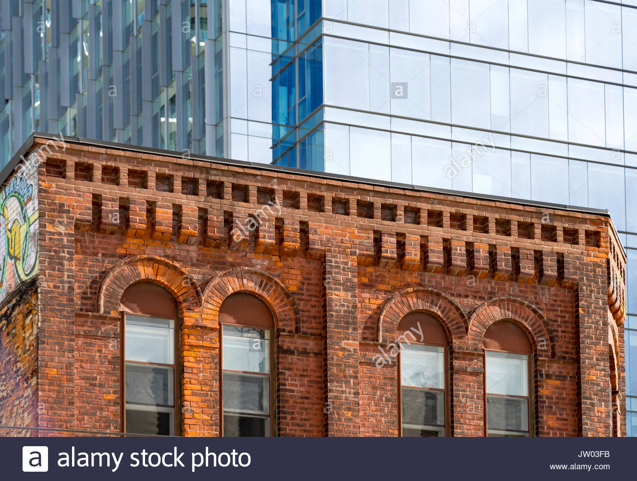 Victorian architecture red brick buildings in Queen Street West contrasting with modern skyscrapers. The heritage Stock Photo