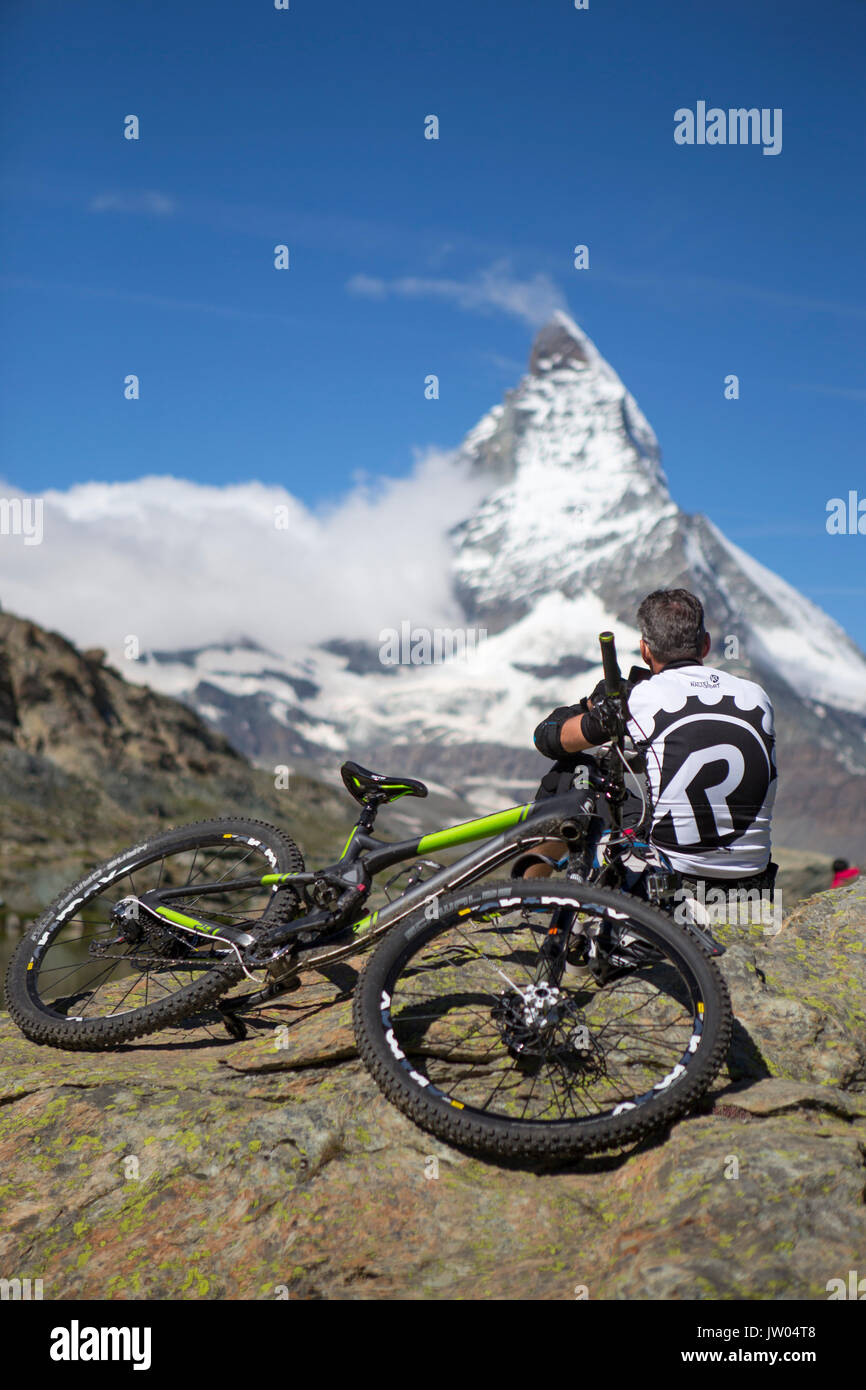 A mountain biker is resting while enjoying the view on the Matterhorn, a famous mountain above Zermatt in the Swiss Alps. - Stock Image