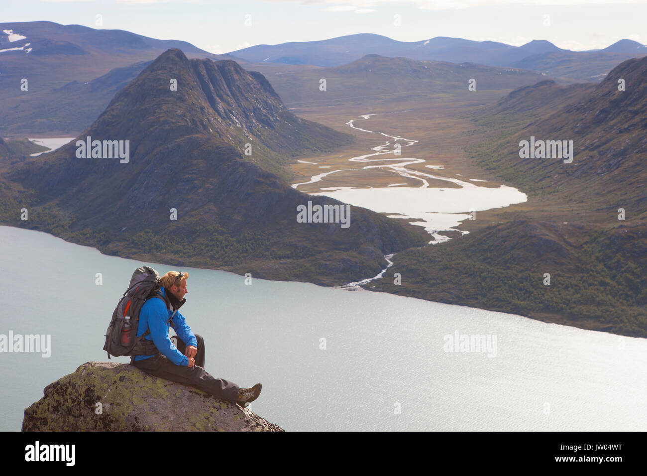 A hiker is enjoying the view over fjords and mountains while sitting on a rock of the famous Besseggen ridge in Norway. This one day traverse in Jotunheimen National Park is the most popular hike in Norway. - Stock Image
