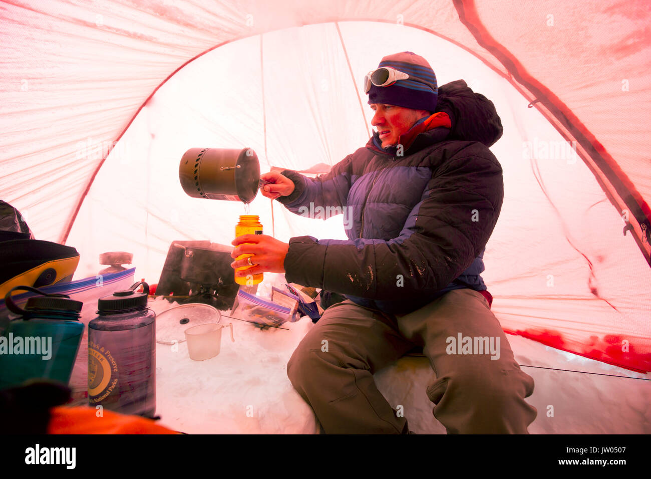 A mountaineers is melting snow to get drinking water, inside a tent at High Camp on Denali in Alaska. Early morning they are going for a summit push to the highest mountain of Northern America. - Stock Image