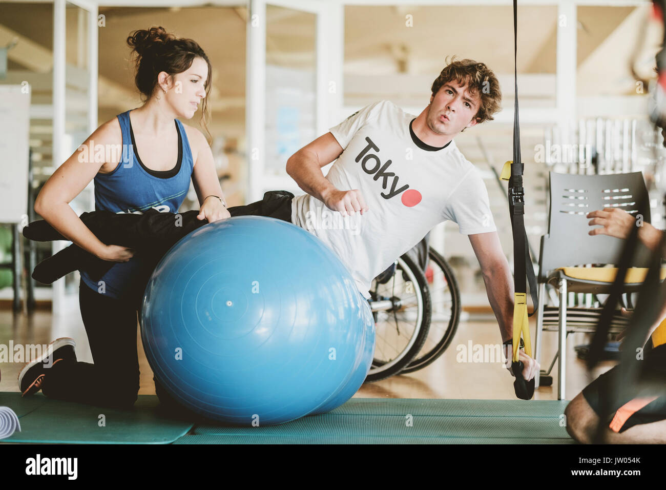 Mid adult man practicing with dumbbells during physiotherapy session Stock Photo