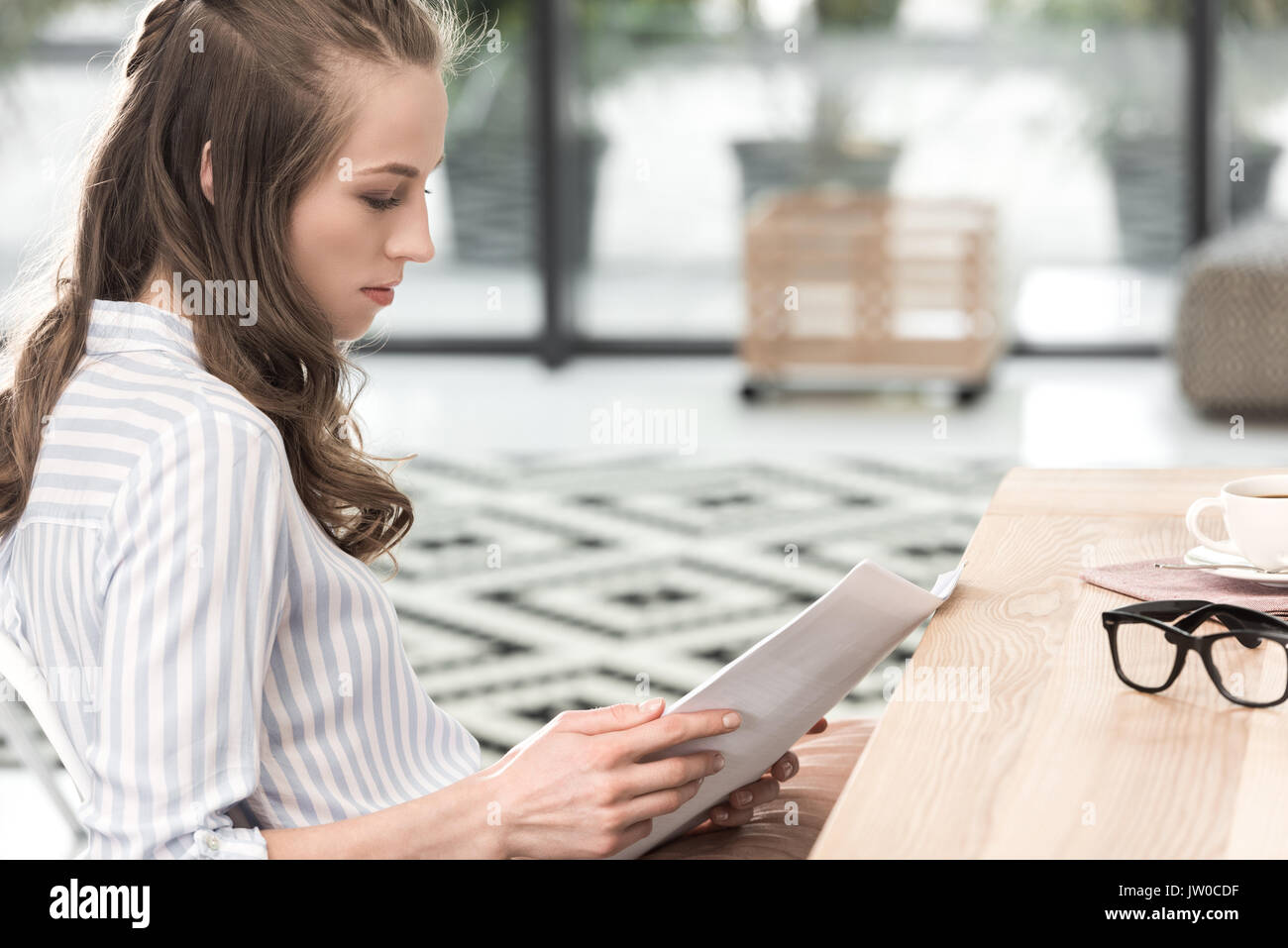 side view of concentrated businesswoman doing paperwork while working in cafe - Stock Image