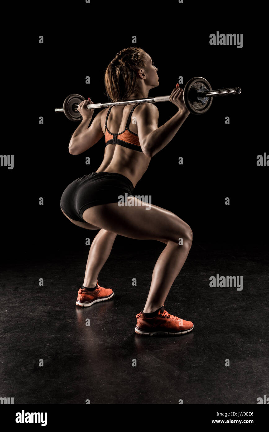 Muscular young woman in sportswear lifting barbell and looking away - Stock Image