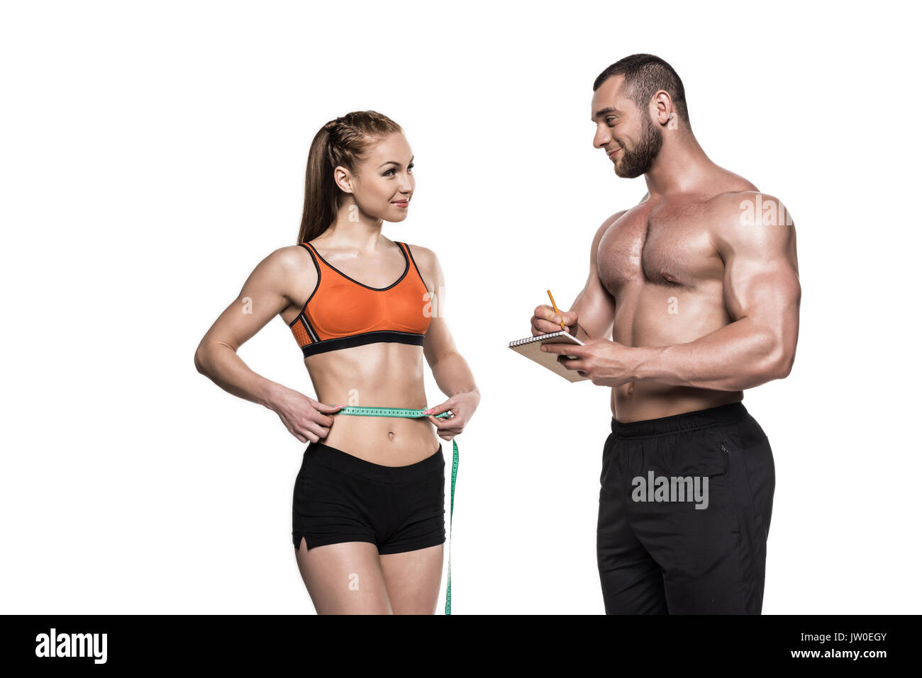 personal trainer writing in notepad while sportswoman measuring her waistline isolated on white - Stock Image