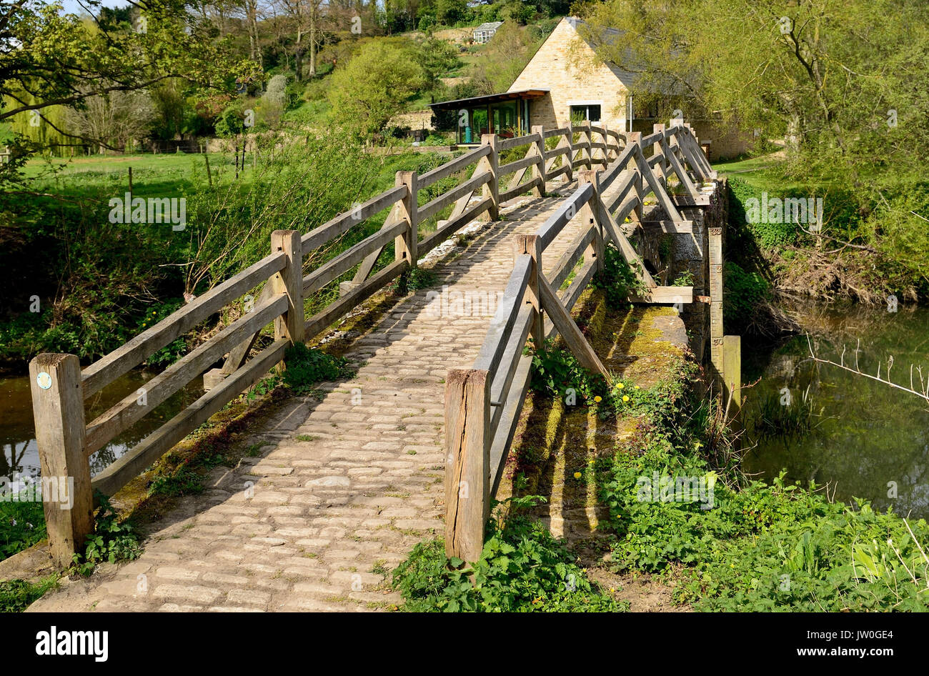 The packhorse bridge over the river Frome at Tellisford spans the county boundary between Wiltshire and Somerset. (Seen from the Wiltshire bank). - Stock Image