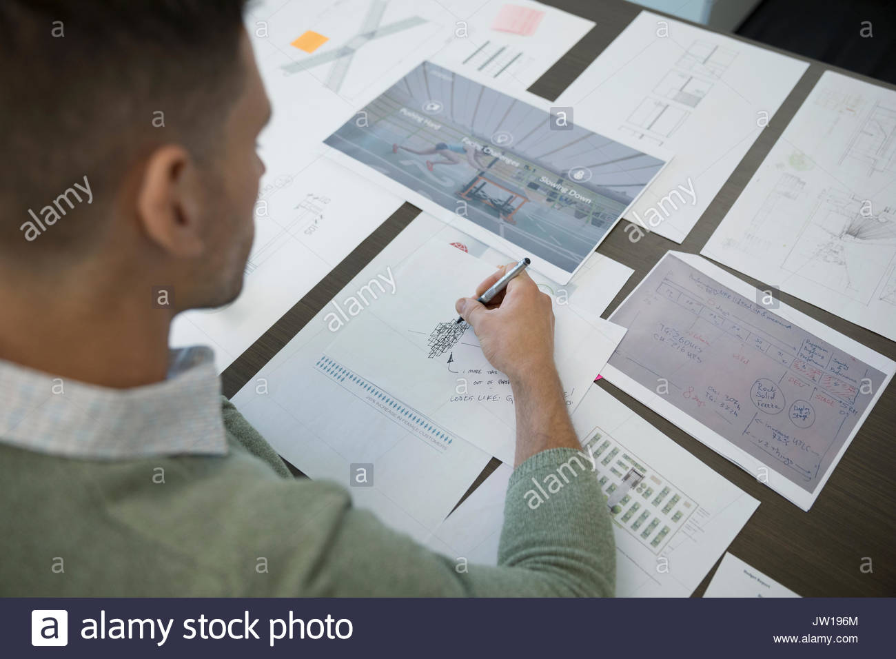 Male architect reviewing blueprints and proofs - Stock Image