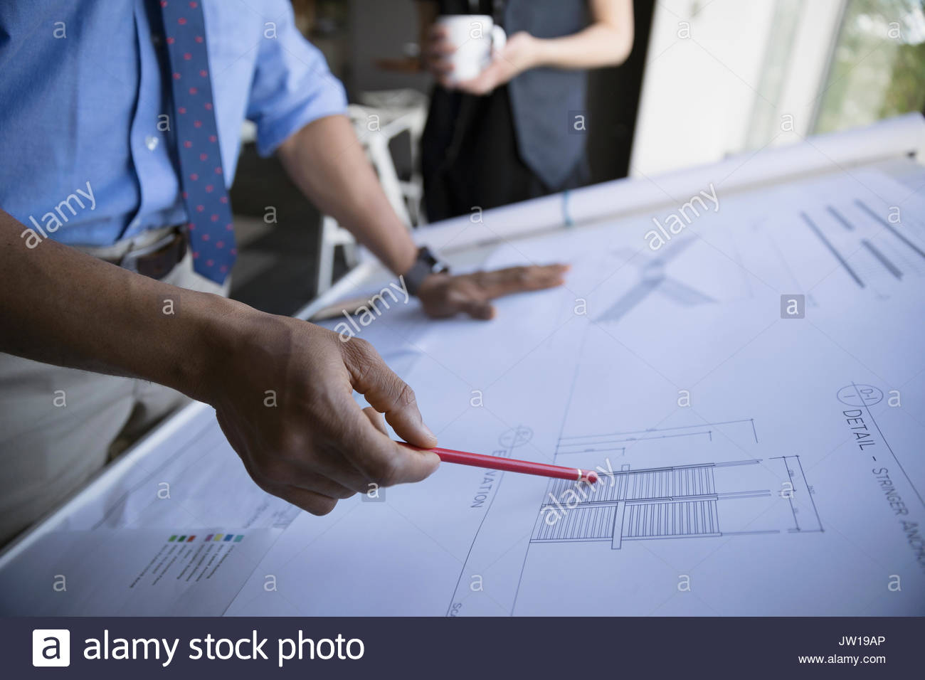 Male architect reviewing blueprints in office - Stock Image