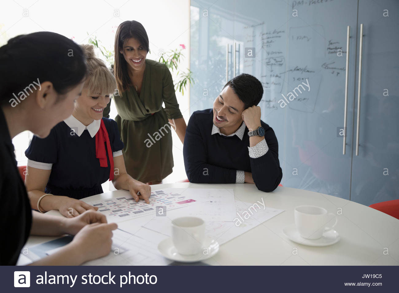 Smiling designers reviewing production schedule in conference room meeting - Stock Image