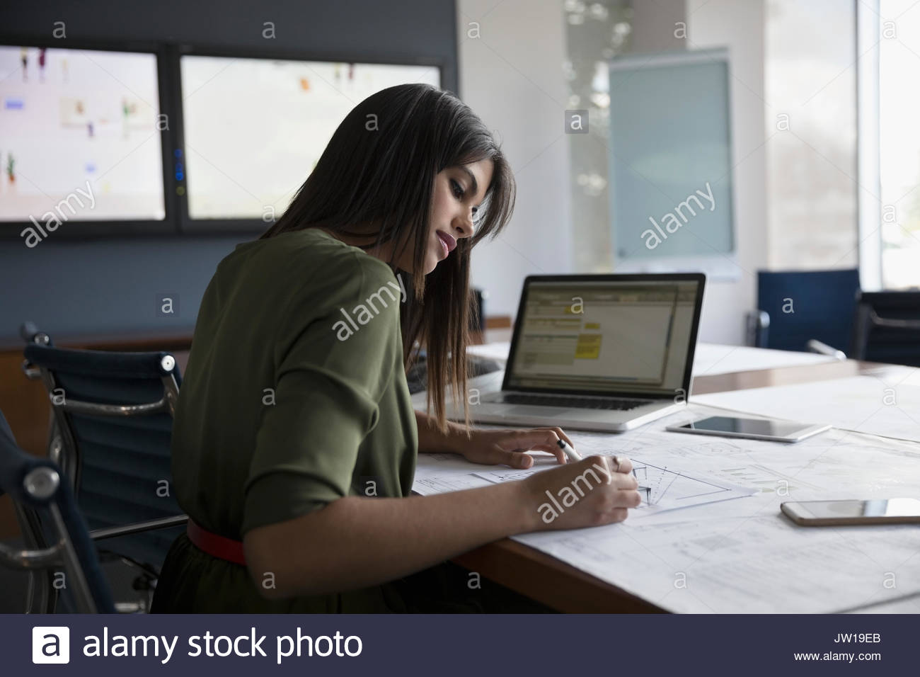 Female architect reviewing and editing blueprints in conference room - Stock Image