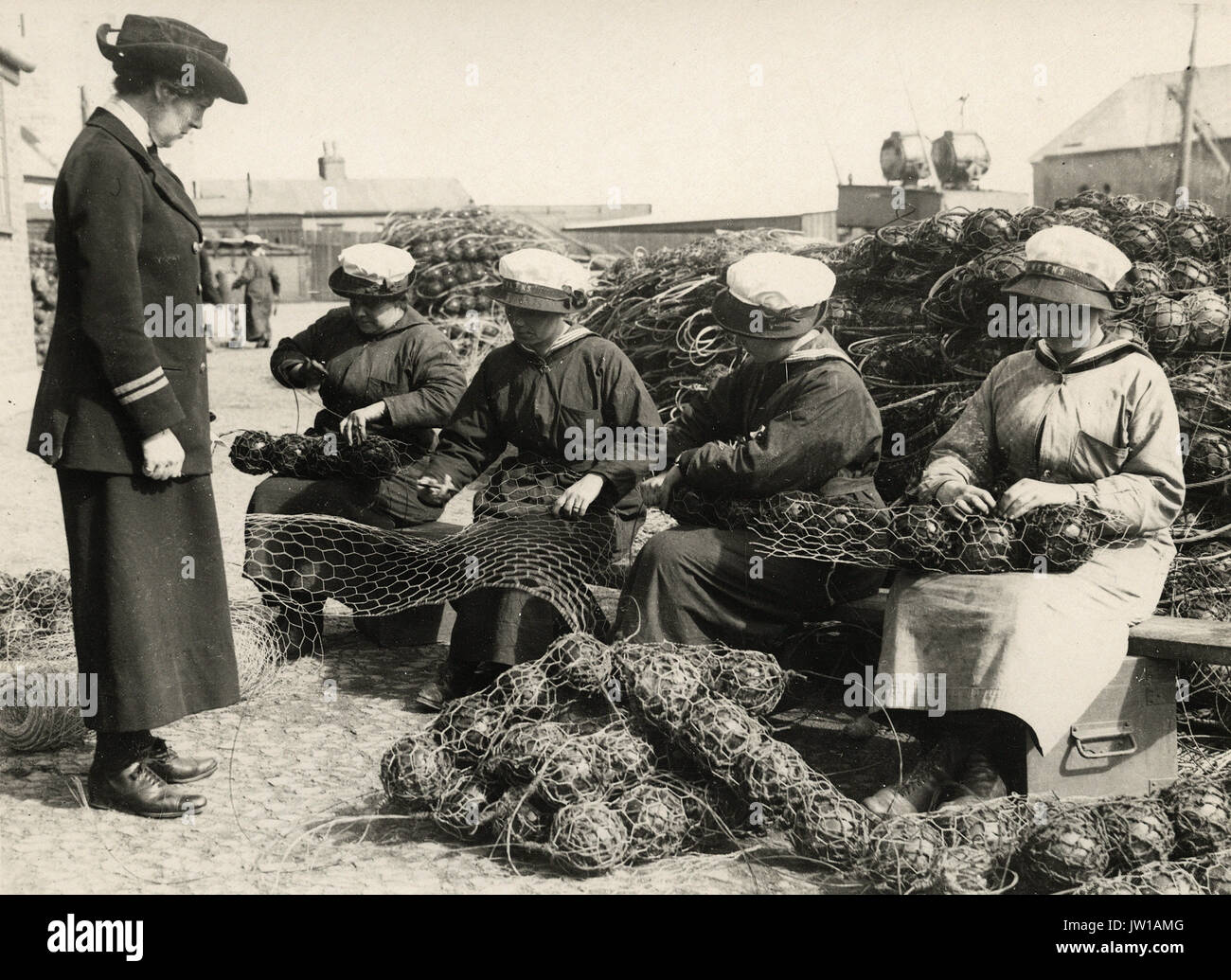 Mine net workers wiring the floats together - Alternative Title: Women's Work - Stock Image