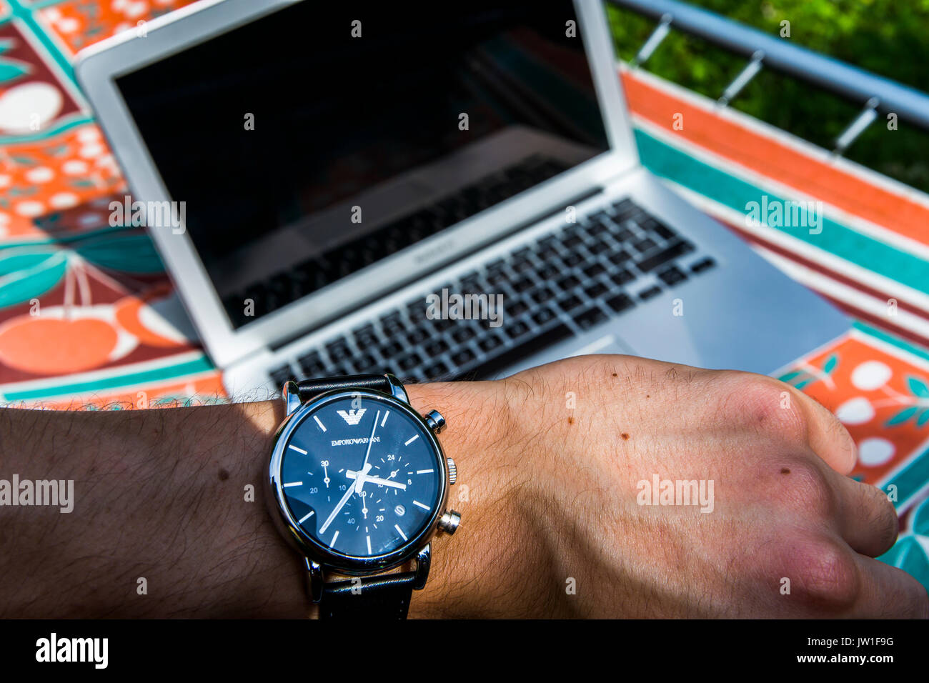 View from person's eyes. Checking hour on a Giorgio Armani watch with a notebook laying on a sunbed in the background. Stock Photo