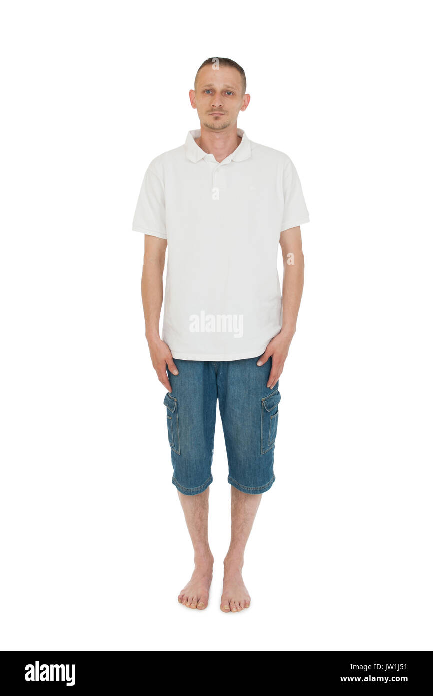 Frontal full-body view of a middle-aged man barefoot on white background seriously looking into the camera. - Stock Image