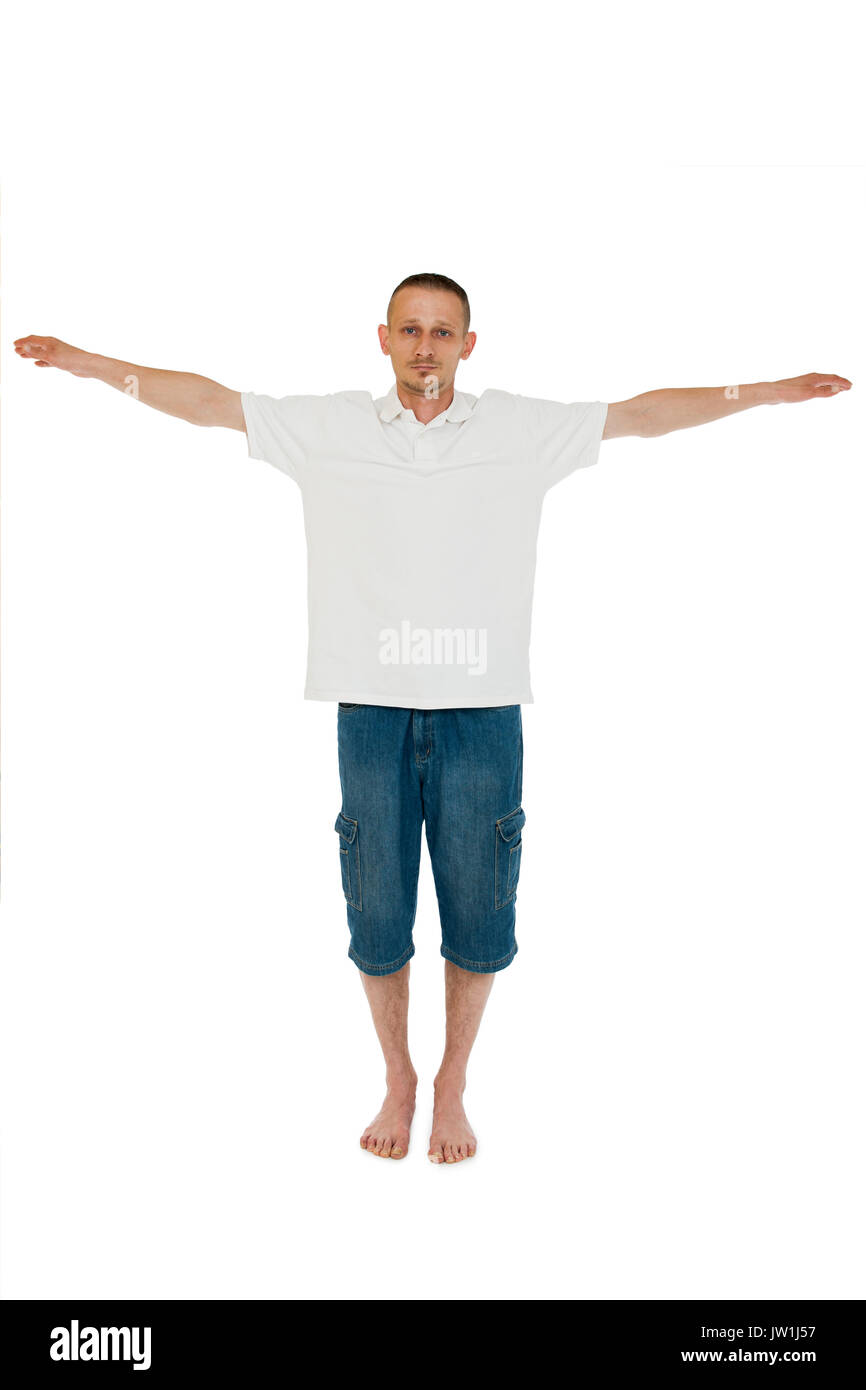 Frontal full-body view of a middle-aged man barefoot on white background seriously looking at the camera with lateral outstretched arms. - Stock Image