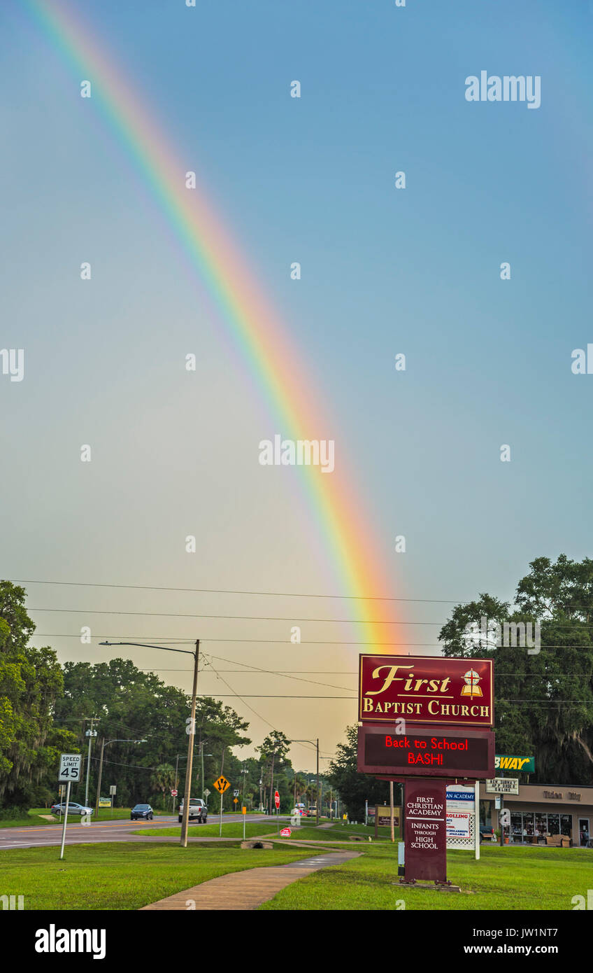 Church sign with rainbow in the background. - Stock Image