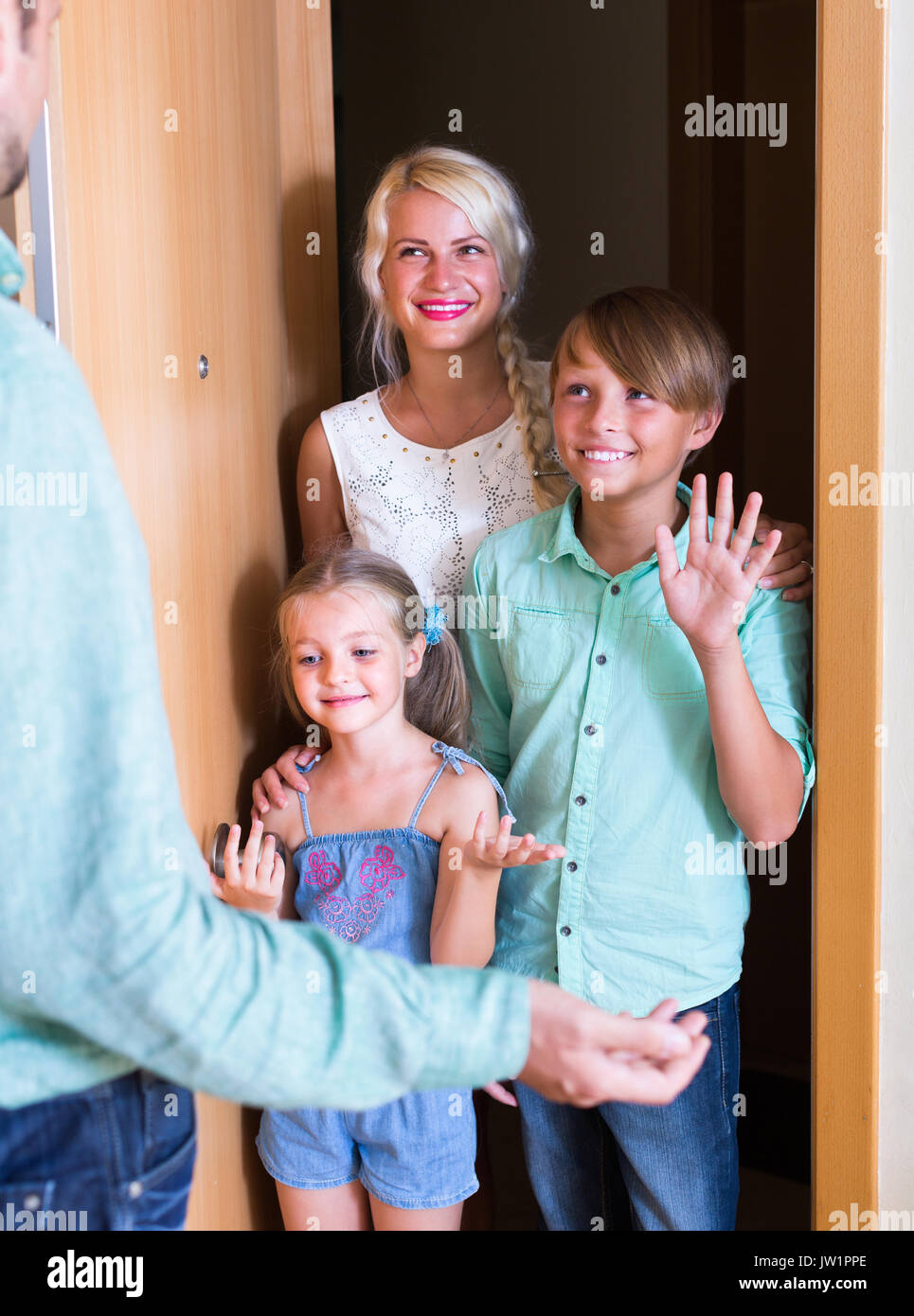 Hospitable man greeting happy smiling guests at apartment entrance Stock Photo