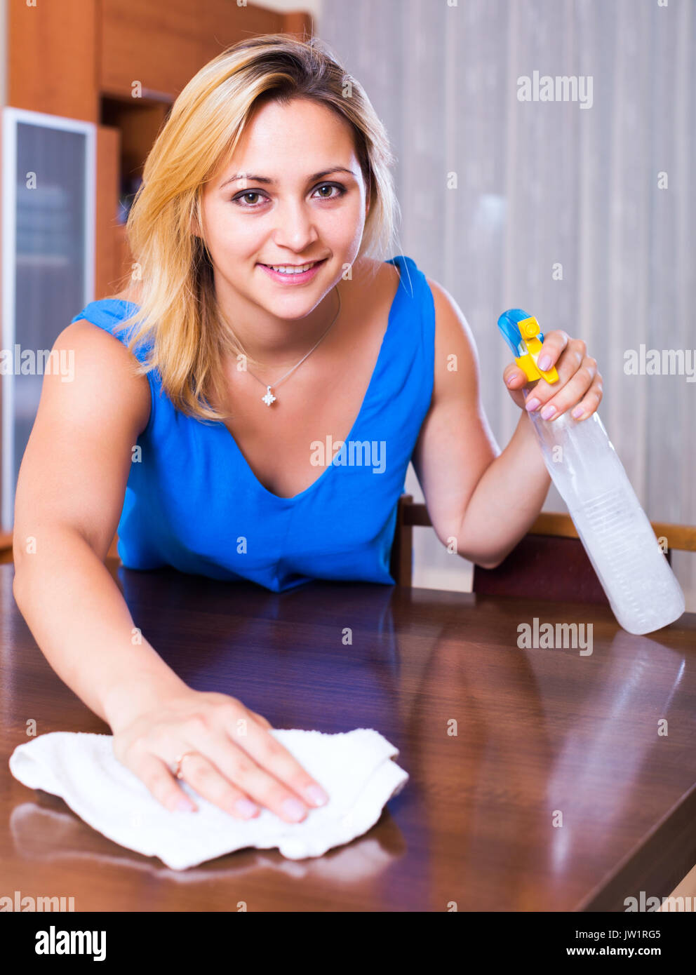 dusting furniture. Dusting Furniture. Portrait Of Ordinary Girl In Blue Blouse Furniture Indoors - Stock Image H