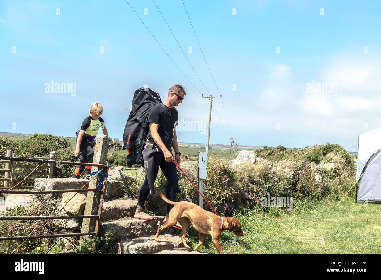 Father, son and dog, climbing stone steps after returning from Gwynver Beach, Sennen, near Penzance, Cornwall, England, UK. - Stock Image