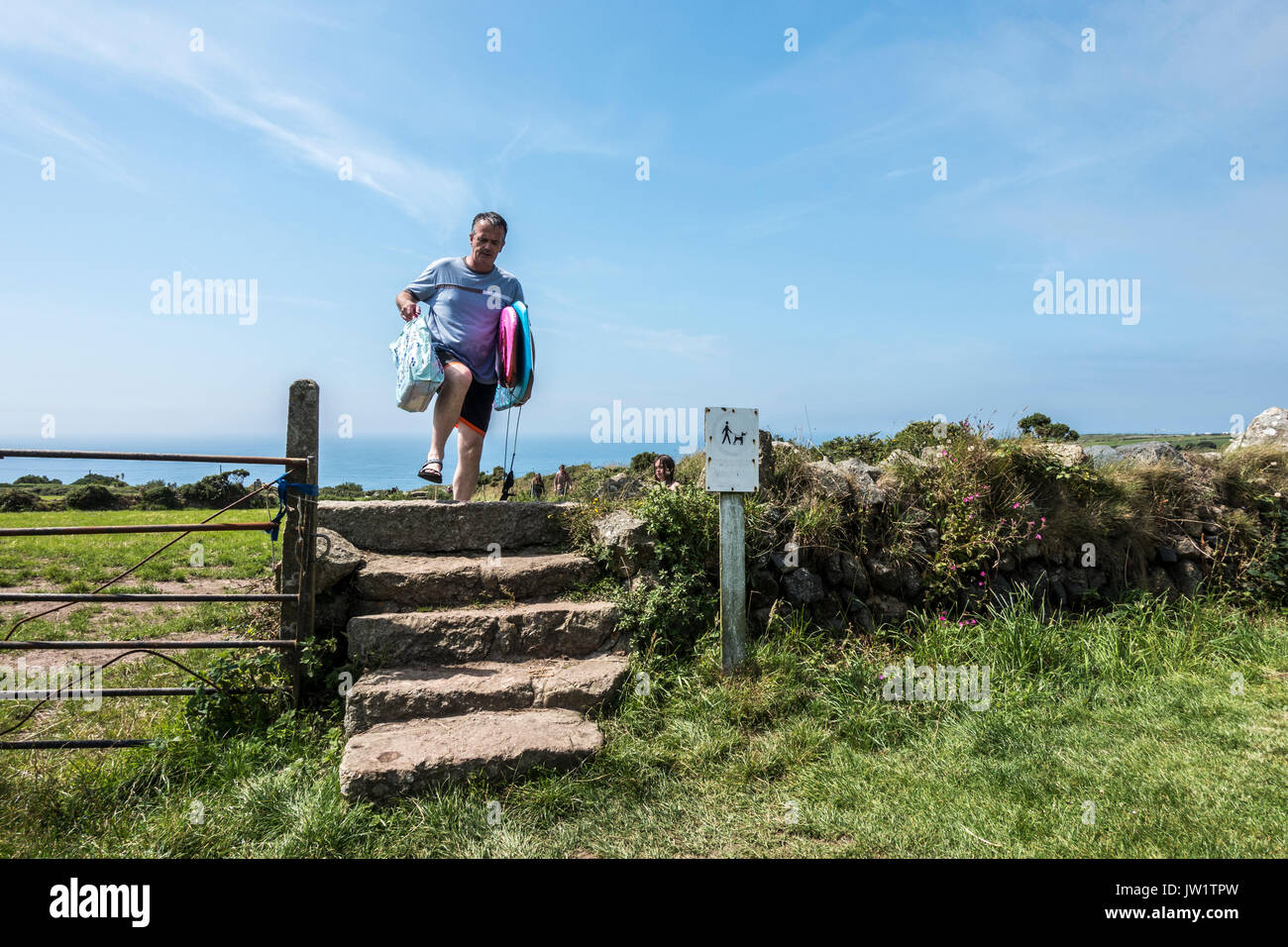 A man carrying surfboards while climbing stone steps, after returning from Gwynver Beach, Sennen, near Penzance, Cornwall, England, UK. - Stock Image
