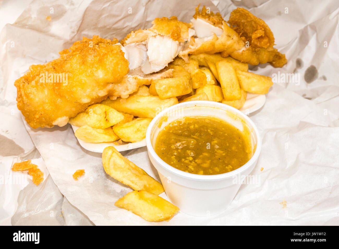 Traditional British takeaway meal of battered fish and chips, plus curry sauce in the containers and paper wrapping. - Stock Image