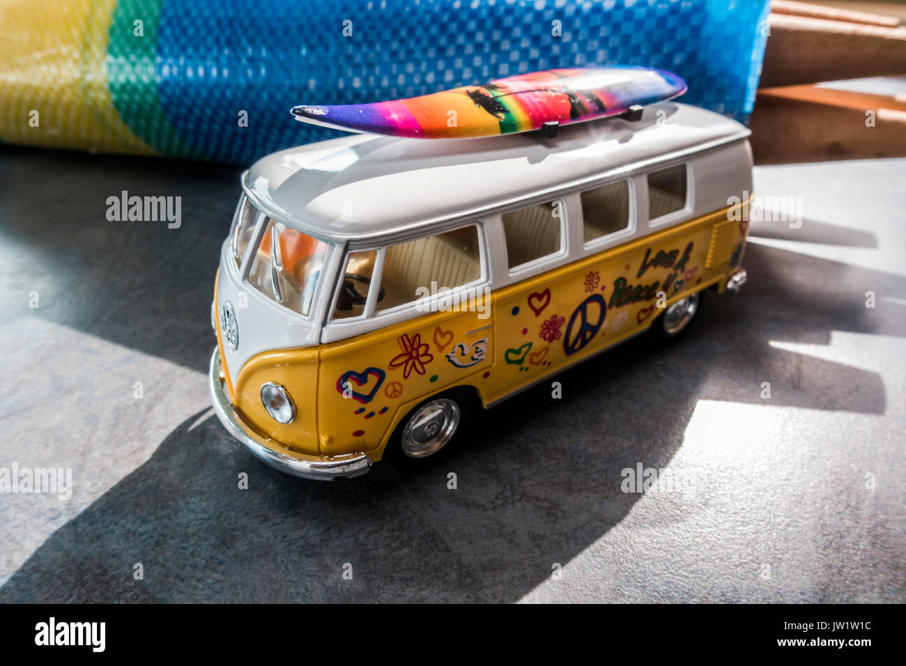 Motorhoming holiday concept with a model VW campervan and surboard on roof, next to a windbreak. - Stock Image
