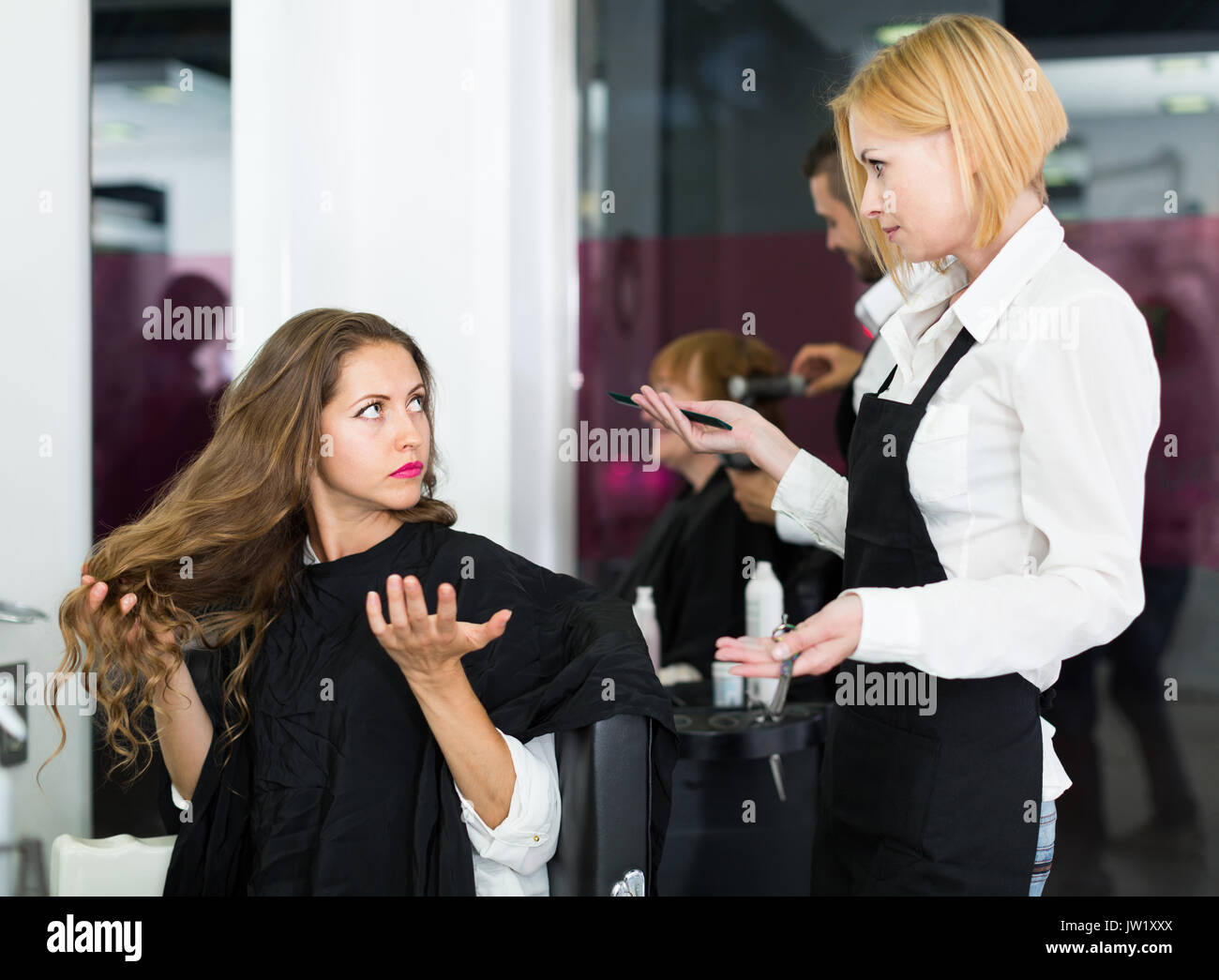 Barber quarrels with the female client about haircut in the barbershop - Stock Image
