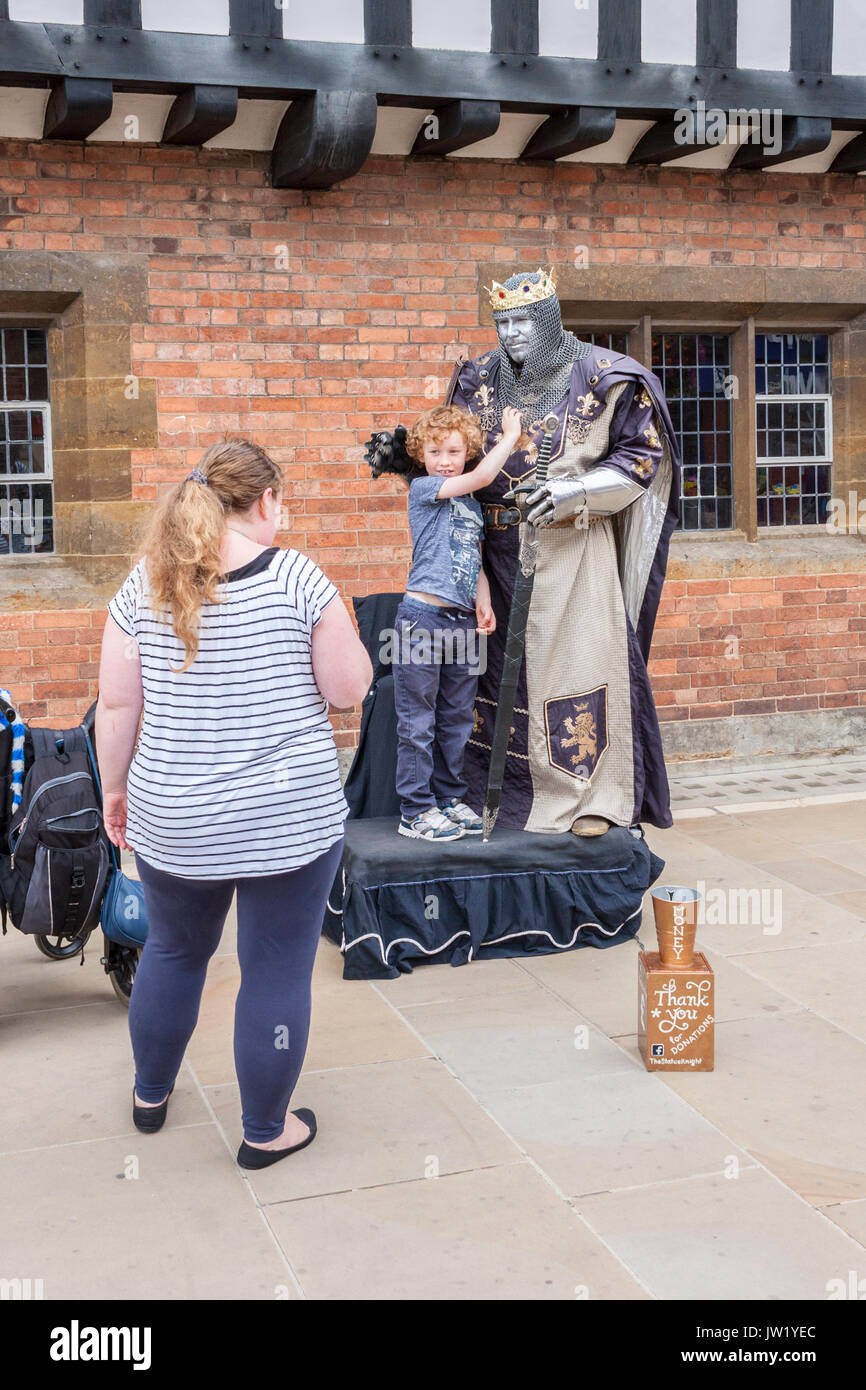A boy has his photo taken with a living statue mime artist in Stratford-upon-Avon - Stock Image