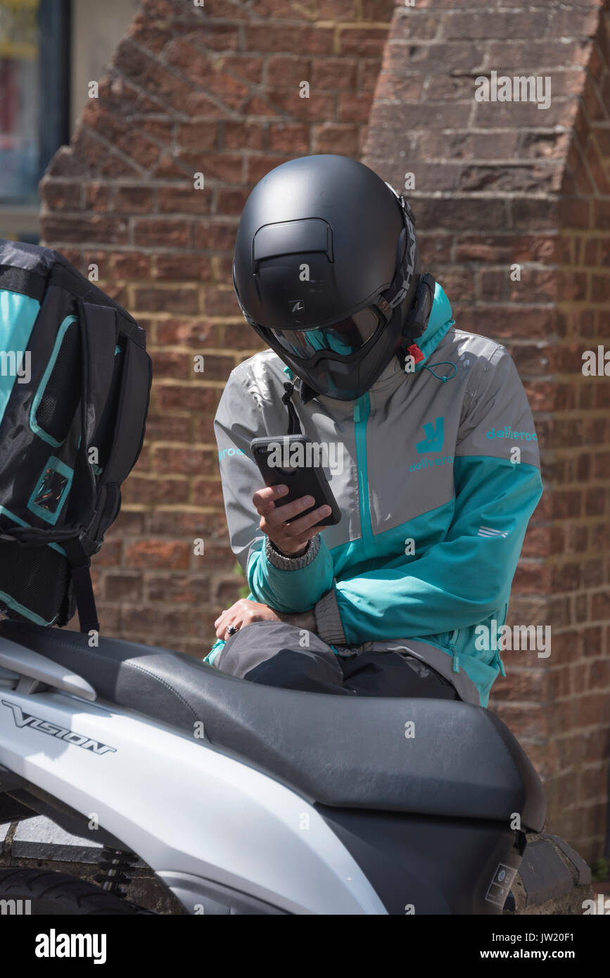 Delivery rider checking his phone for the next job - Stock Image