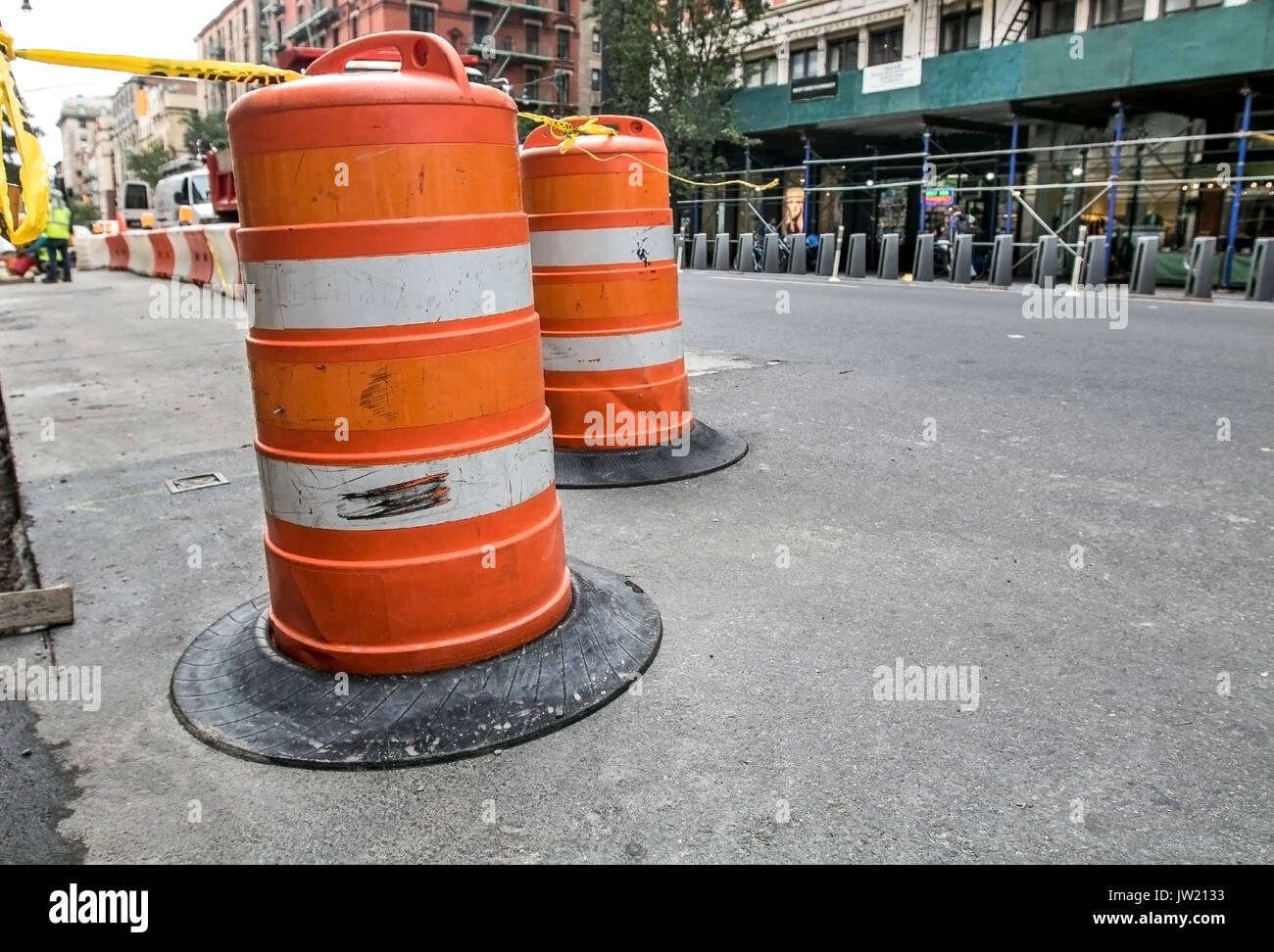 A traffic barricade of orange barrels indicates a site of road construction work in Manhattan. - Stock Image