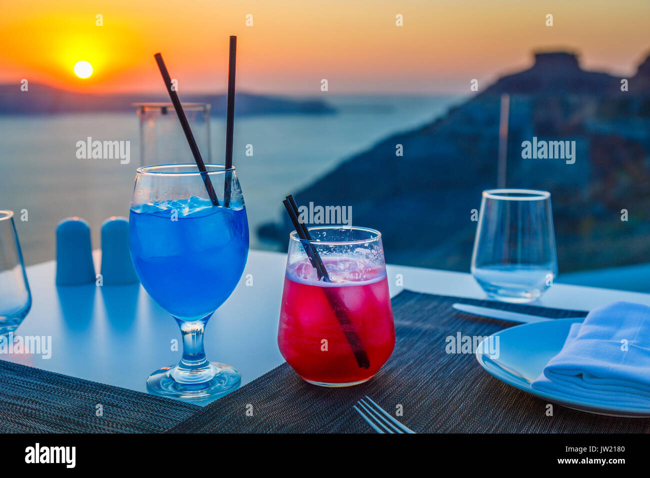 Colourful cocktails, Imerovigli in the evening, a village near Fira on the Greek island of Santorini called 'the balcony to the Aegean' for its sunset - Stock Image