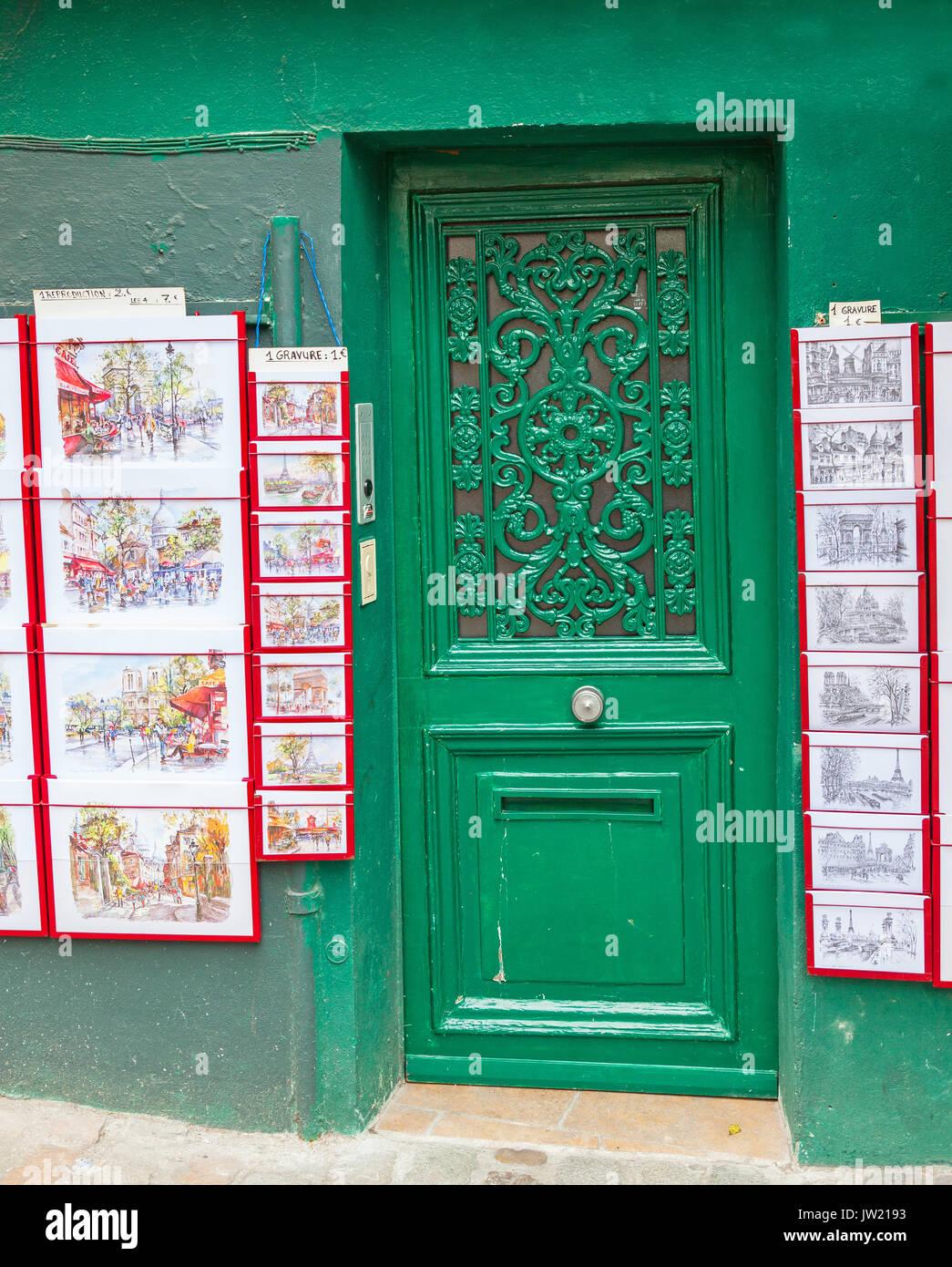 A green door bracketed by art prints in Montmartre in Paris. - Stock Image