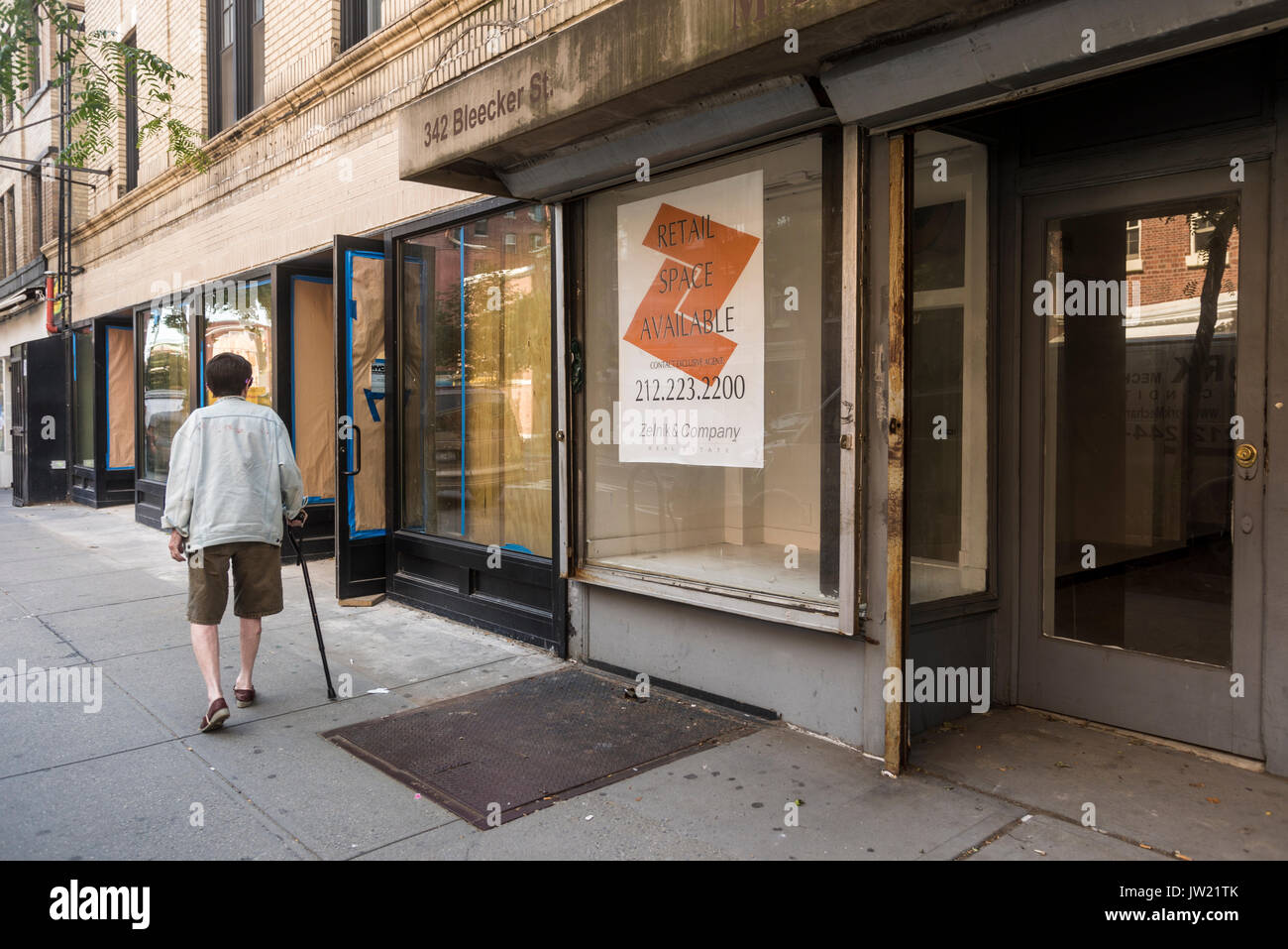 New York, NY, USA - An elderly woman with a cane walks past some of the many empty storefronts for lease on Bleecker Street that remains vacant due to high rent. ©Stacy Walsh Rosenstock - Stock Image