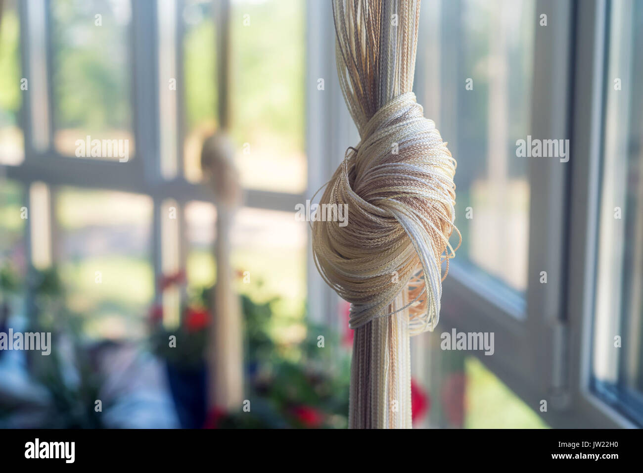 Beige curtain tied in knot - Stock Image