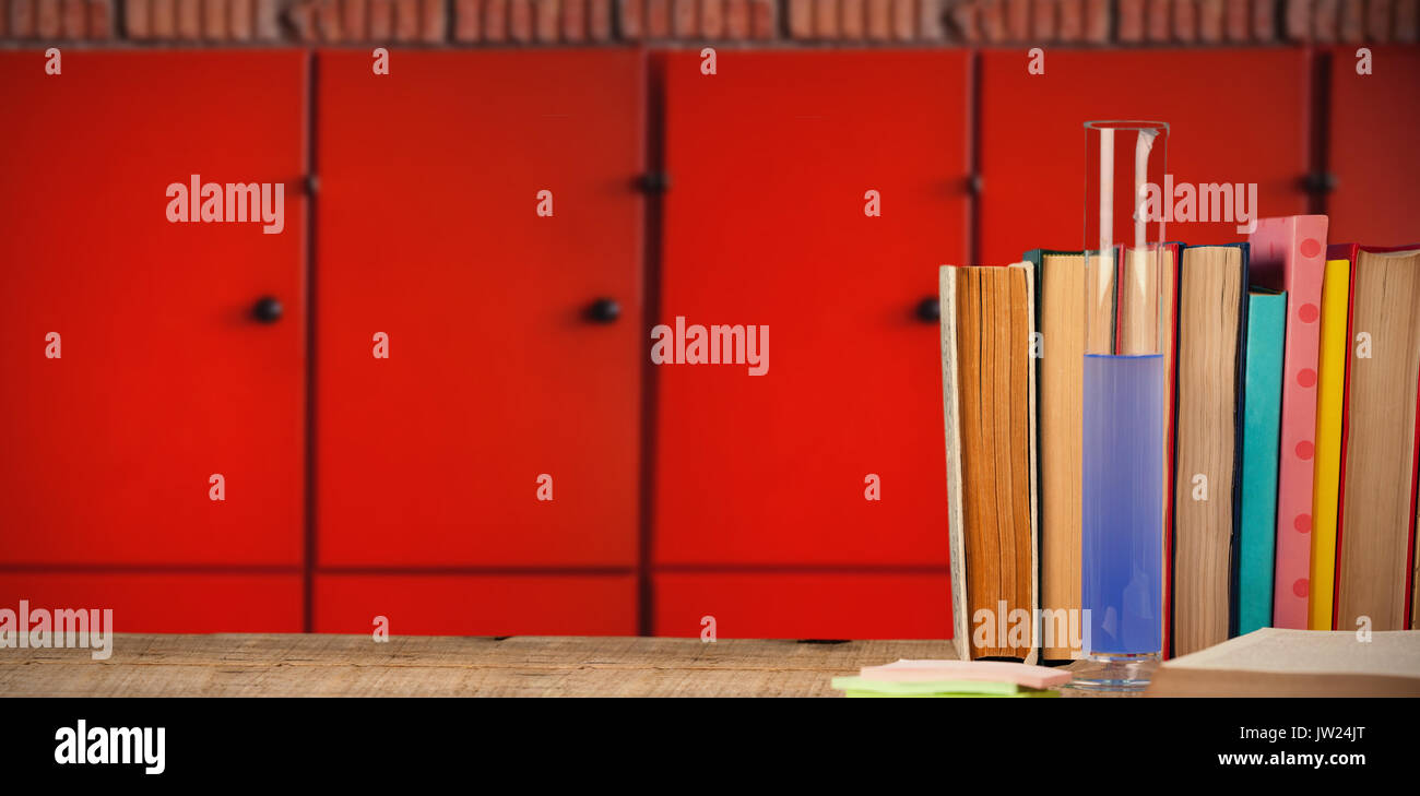 Books arranged on wooden table against close-up of orange lockers - Stock Image