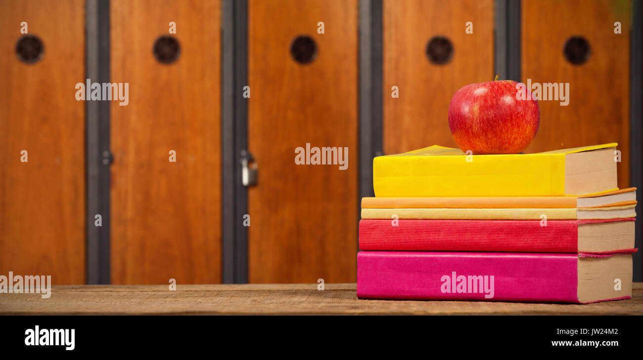 Apple with books on wooden table against close-up of brown lockers - Stock Image