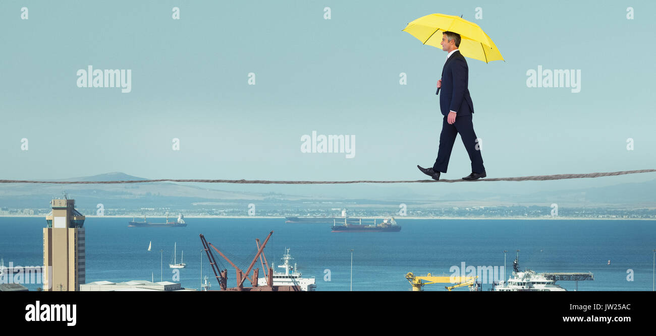Businessman with yellow umbrella walking on white background against view of harbor - Stock Image