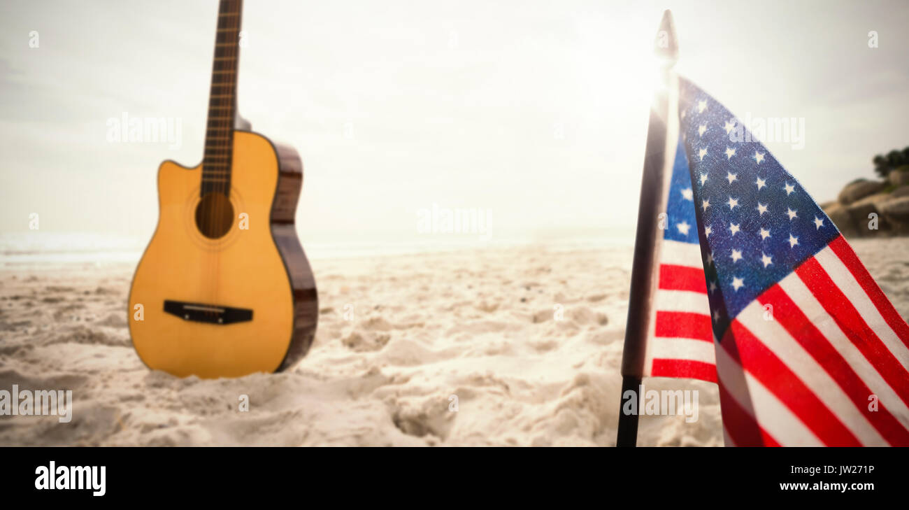 A white flash with a black blackground against acoustic guitar in sand Stock Photo