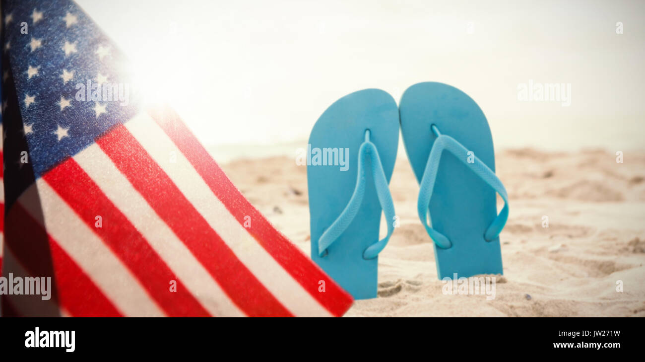 A white flash with a black blackground against blue flip flop in sand - Stock Image