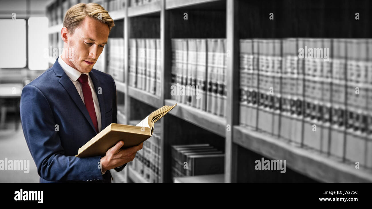 Handsome lawyer reading in law library at university - Stock Image