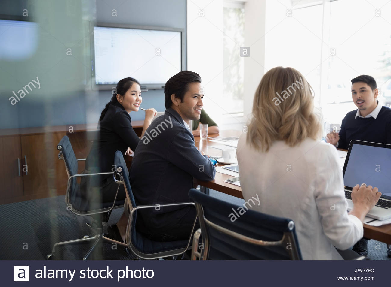 Business people talking, using laptop in conference room meeting - Stock Image