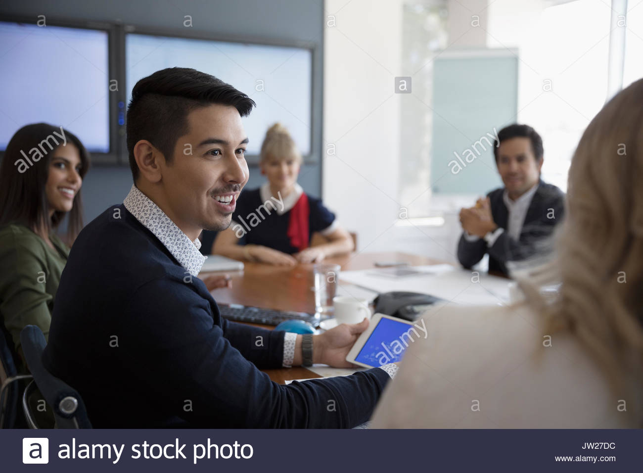 Smiling businessman talking to coworker in conference room meeting - Stock Image