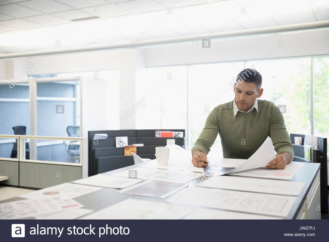 Male architect reviewing blueprints at table in office - Stock Image