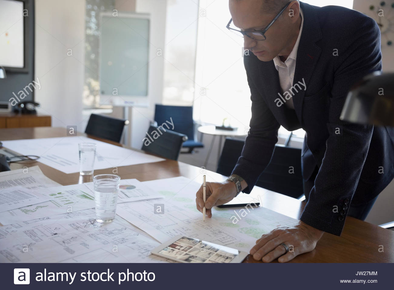 Male architect reviewing, editing blueprints in conference room - Stock Image