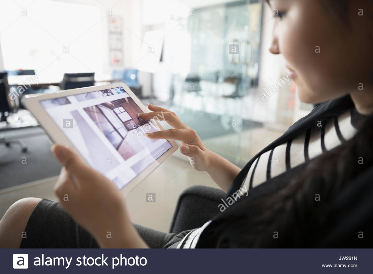 Female designer reviewing digital photographs on digital tablet in office Stock Photo
