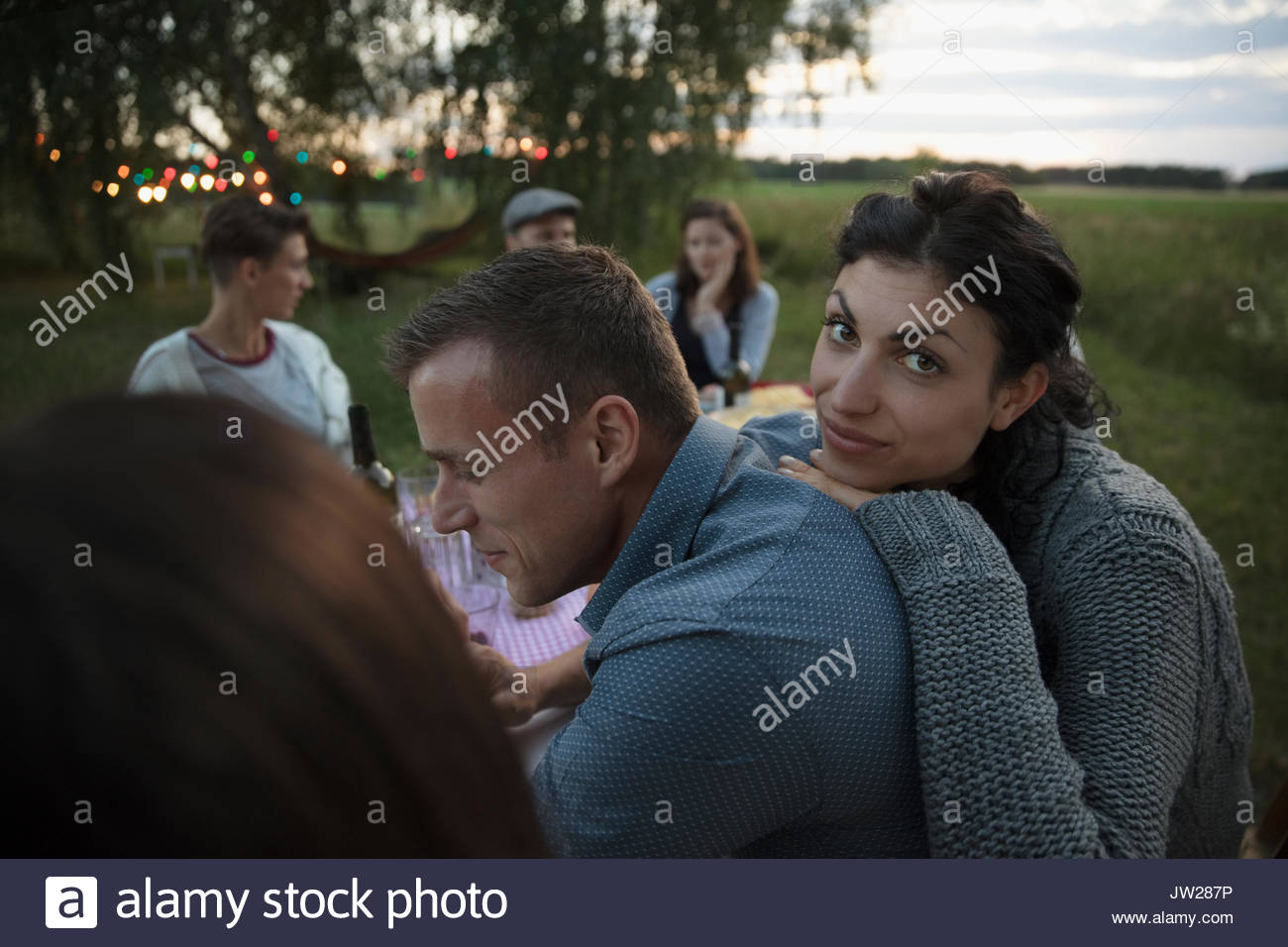 Portrait woman leaning on boyfriend at summer garden party dinner - Stock Image