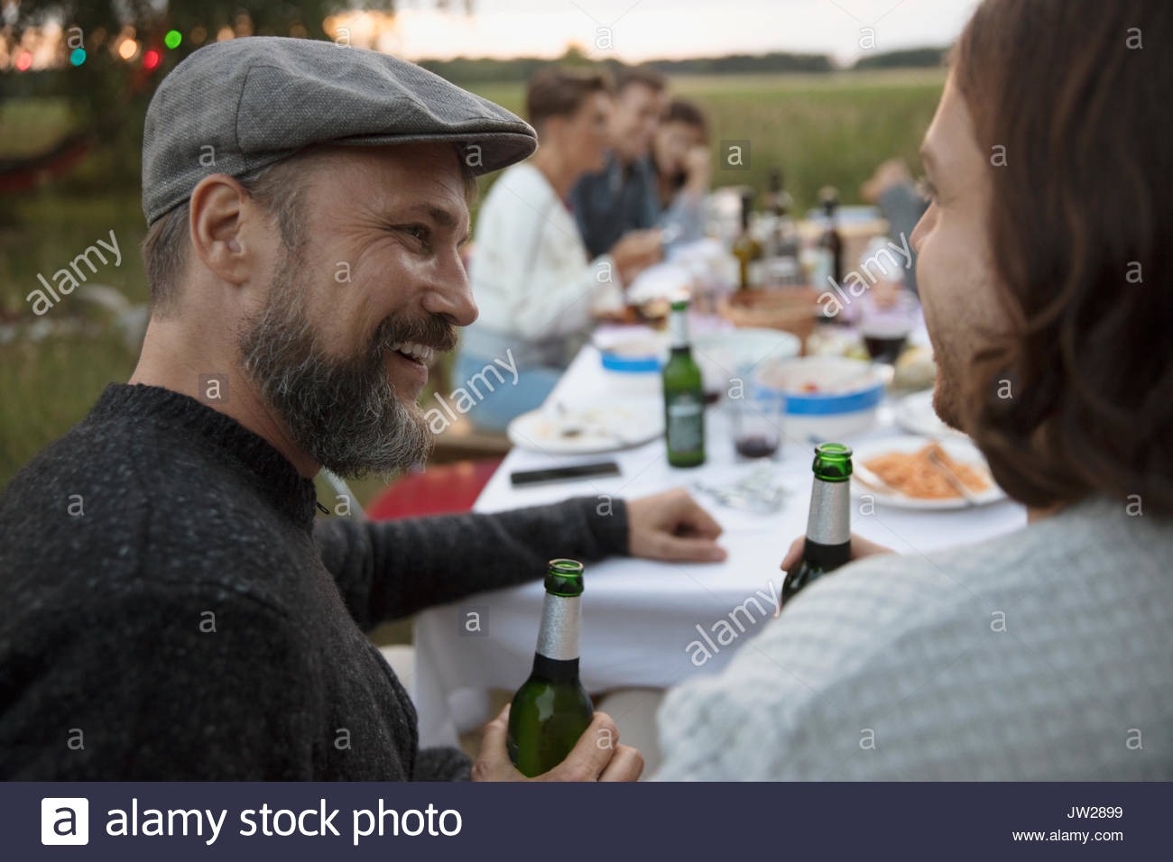 Smiling man drinking beer and talking to friend at summer garden party dinner - Stock Image