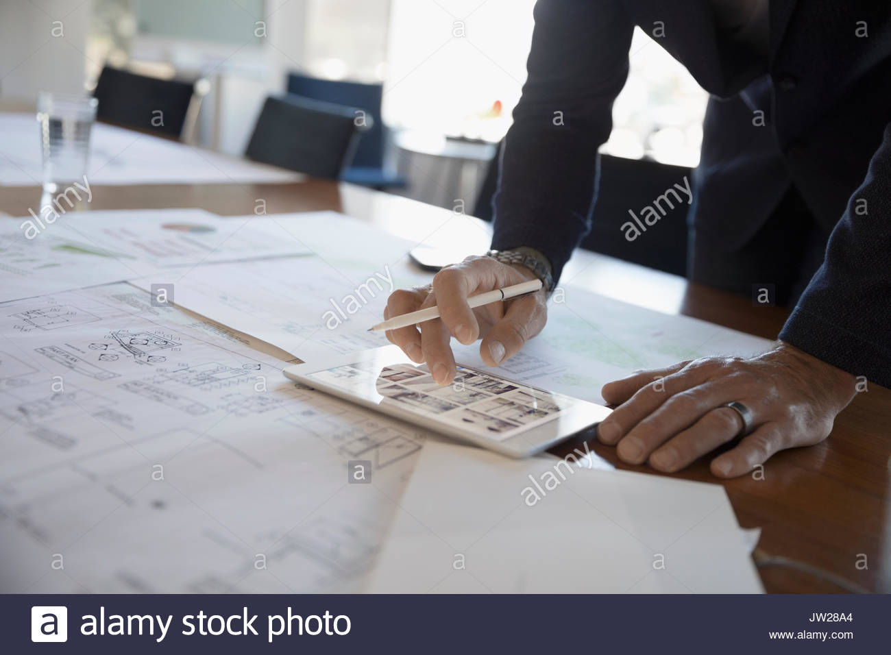 Businessman reviewing, editing paper and digital blueprints on digital tablet in conference room - Stock Image