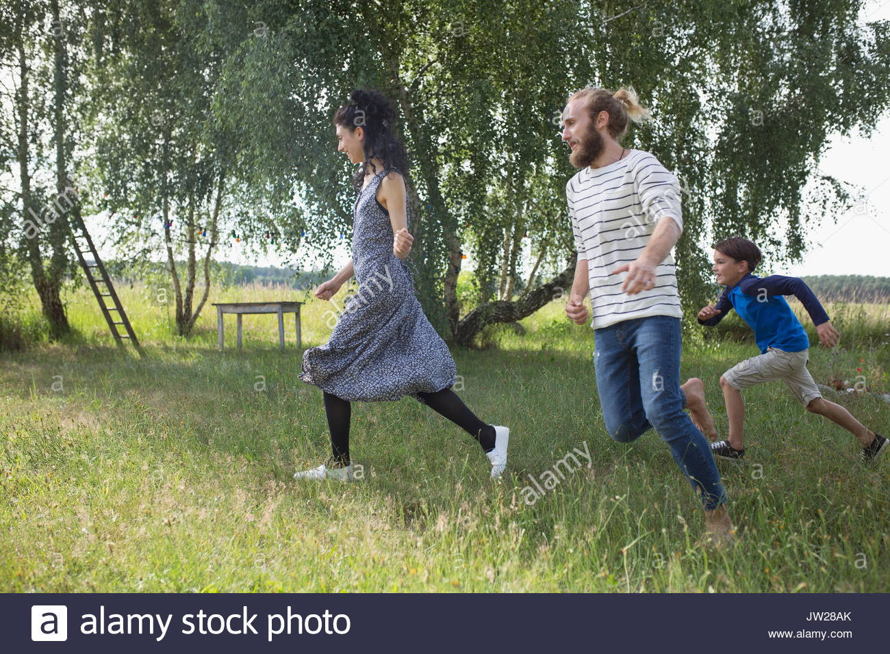 Playful family running in rural yard - Stock Image