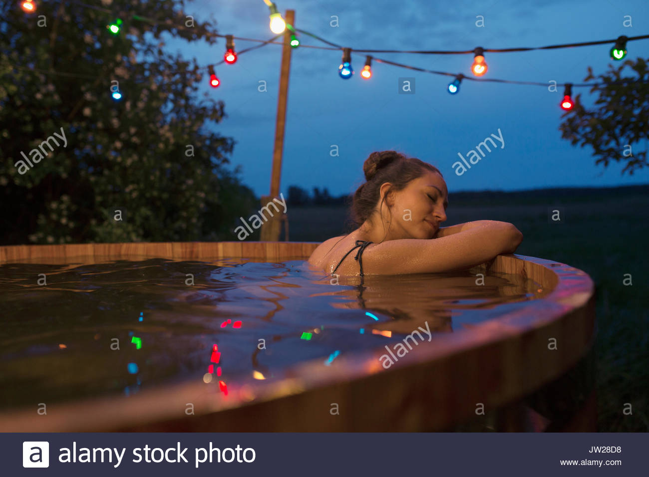Serene young woman relaxing, soaking in hot tub under string lights ...