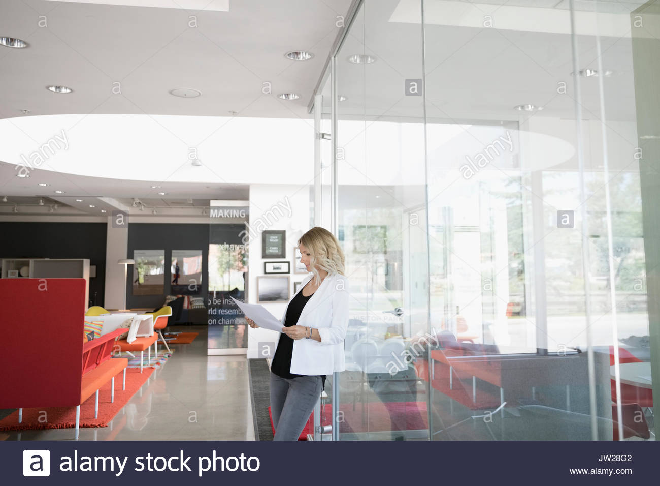 Businesswoman reading paperwork outside conference room in office - Stock Image