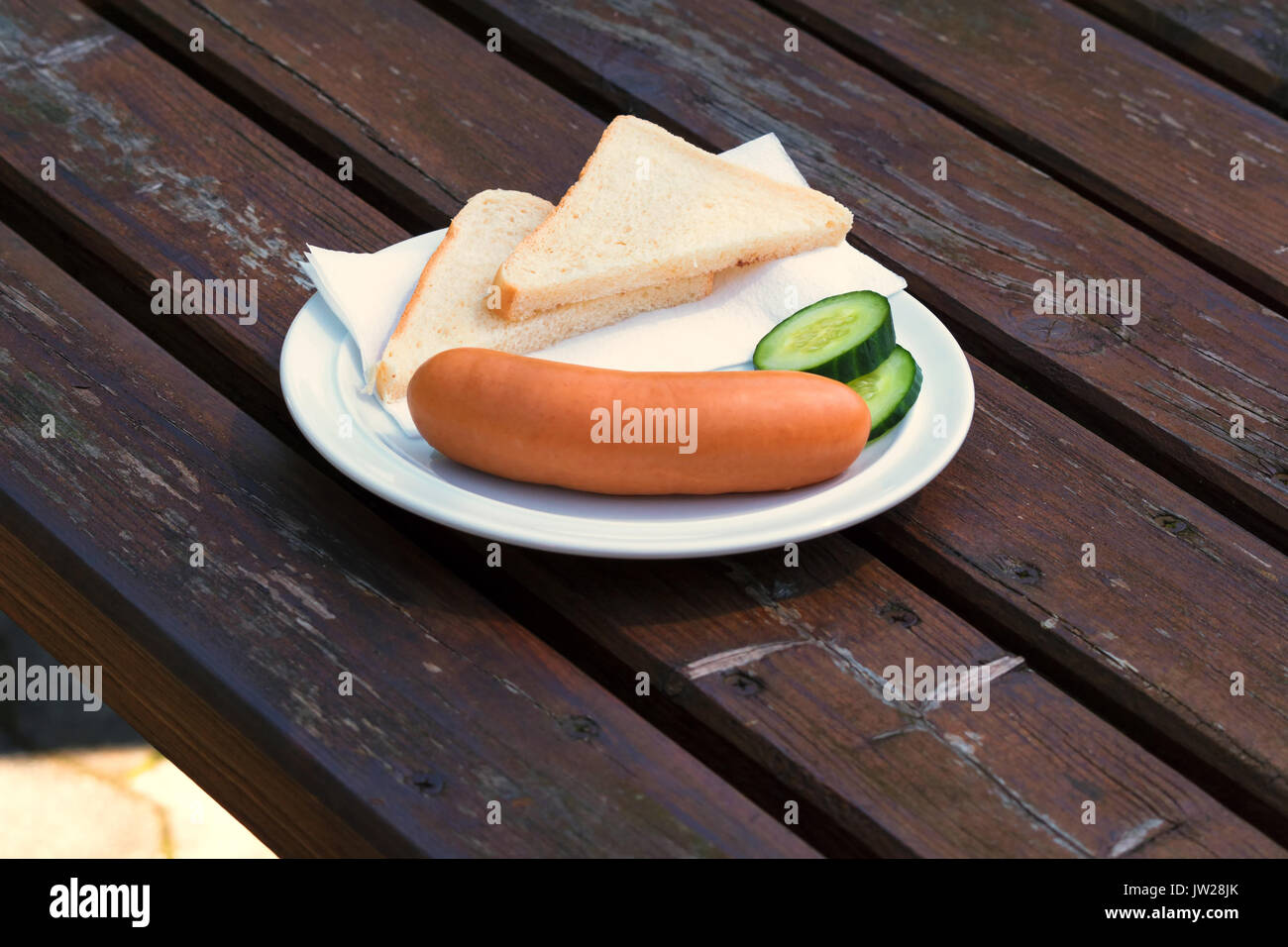 Bock sausage, wieners or Frankfurther sausage with toast and cucumbers on a white plate. Stock Photo